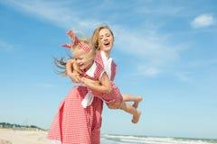 Moeder en haar dochter die pret op het strand hebben Stock Foto
