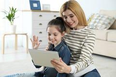 Moeder en haar dochter die videopraatje op tablet gebruiken stock afbeeldingen