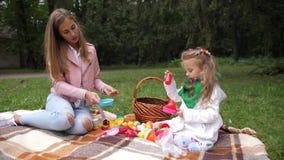Moeder en haar dochtermeisje die in een de herfstpark spelen Plastic speelgoed 4K Langzame Motie stock footage
