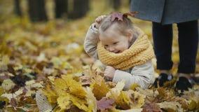 Moeder en haar dochtermeisje die in een de herfstpark spelen - werp de bladeren, babygelach stock video