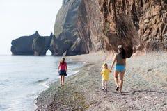 Moeder en haar dochters die bij het overzees lopen Royalty-vrije Stock Foto's