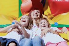 Moeder en haar dochters die pret bij het springen van kasteel hebben Stock Foto's