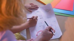 Moeder en haar jong geitje die op papier trekken of kunstthuiswerk doen die samen, bij lijst thuis zitten, hoogste schot stock footage