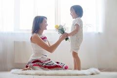 Moeder en haar kind, omhelzend met tederheid en zorg Stock Foto's