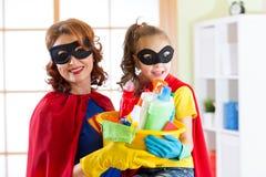 Moeder en haar kind in Superhero-kostuums Mamma en jong geitje klaar om het schoonmaken te huisvesten Huishoudelijk werk en huish stock afbeeldingen