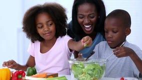Moeder en haar kinderen die groenten voorbereiden stock videobeelden