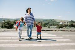 Moeder en haar kinderen die weg kruisen Stock Foto's