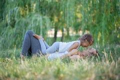 Moeder en haar meisje op de groene weide die van het de zomergras pret hebben Stock Afbeeldingen