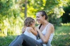 Moeder en haar meisje op de groene weide die van het de zomergras pret hebben Royalty-vrije Stock Afbeelding