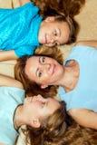 Moeder en haar twee dochters die op de vloer liggen Stock Afbeelding
