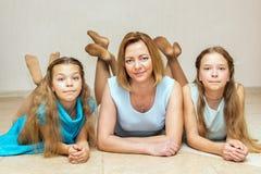 Moeder en haar twee dochters die op de vloer liggen Royalty-vrije Stock Afbeeldingen