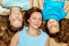 Moeder en haar twee dochters die op de vloer liggen Stock Foto's
