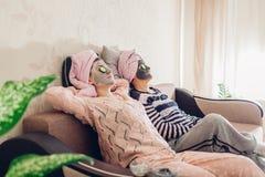 Moeder en haar volwassen dochter die met gezichts toegepaste maskers en komkommers ontspannen Vrouwen die en pret thuis koelen he royalty-vrije stock afbeeldingen