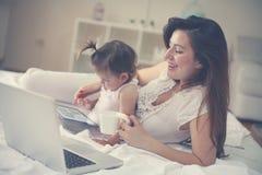 Moeder en haar weinig baby thuis Moeder en baby die techno gebruiken royalty-vrije stock foto