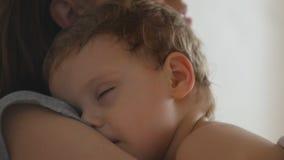 Moeder en haar weinig babyjongen in bed in zonnige ruimte stock video