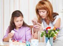 Moeder en haar weinig dochter die op Paaseieren schilderen Royalty-vrije Stock Foto