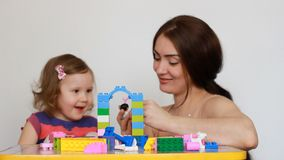 Moeder en haar weinig dochter die samen het zitten spelen bij de lijst Meisje bezig met zijn aannemer, mamma stock video