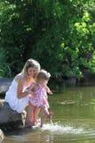 Moeder en haar weinig dochter die water spuiten bij het meer Royalty-vrije Stock Fotografie