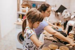 Moeder en haar weinig dochter kokende pannekoeken voor het ontbijt in de kleine comfortabele keuken stock afbeelding