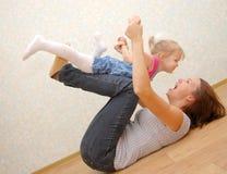 Moeder en haar weinig dochter op houten vloer royalty-vrije stock fotografie