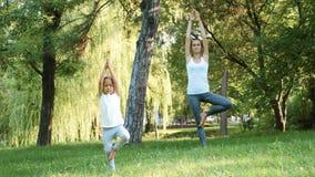 Moeder en haar weinig leuke dochter die yogaoefening samen doen stock videobeelden