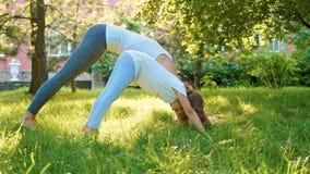 Moeder en haar weinig leuke dochter die yogaoefening samen doen stock foto's