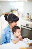 Moeder en haar weinig zoon die ontbijt hebben Stock Foto's