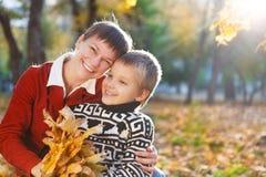 Moeder en haar zoon die in de herfst lopen Stock Afbeeldingen