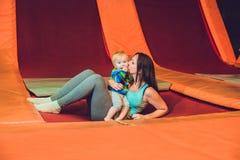 Moeder en haar zoon die op een trampoline in geschiktheidspark springen en exersice binnen doen royalty-vrije stock afbeeldingen