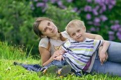 Moeder en haar Zoon die rust in de lentepark hebben stock afbeeldingen