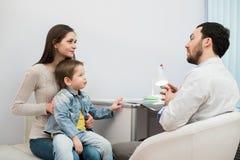 Moeder en haar zoon met grappig gezicht bij het ziekenhuis die aan een arts spreken stock afbeelding