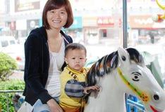Moeder en haar zoon paardrijden Stock Afbeeldingen
