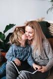 Moeder en het boek van de van de zoonszitting en lezing samen thuis royalty-vrije stock foto's