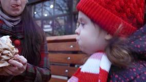 Moeder en ittle leuke het glimlachen meisjeszitting op de bank in het stadspark in de wintertijd De moeder voedt het meisje met stock footage