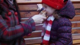Moeder en ittle leuke het glimlachen meisjeszitting op de bank in het stadspark in de wintertijd De moeder voedt het meisje met stock videobeelden