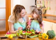 Moeder en jong geitje die en pret in keuken koken hebben royalty-vrije stock afbeelding