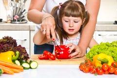 Moeder en jong geitje die gezond voedsel voorbereiden Stock Foto