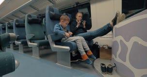 Moeder en jong geitje gebruikend elektronika tijdens treinrit stock video