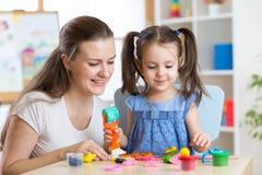 Moeder en jong geitjedochter van klei en spel thuis samen wordt gevormd dat Concept kleuterschool of huisonderwijs Royalty-vrije Stock Afbeelding