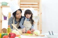 Moeder en jong geitjemeisje die en het snijden groenten koken Stock Foto's