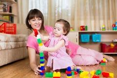 Moeder en jong geitjespelspeelgoed thuis Stock Afbeeldingen