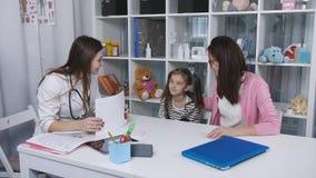 Moeder en jonge dochter aan de arts Een vrouw met een kleine die dochter op het kantoor van het kind wordt onderzocht stock videobeelden
