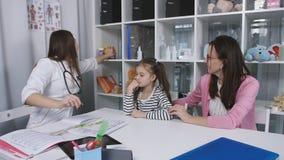 Moeder en jonge dochter aan de arts Een vrouw met een kleine die dochter op het kantoor van het kind wordt onderzocht stock video