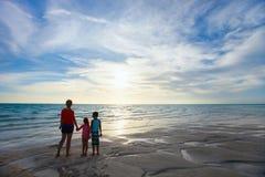 Moeder en jonge geitjes bij strandsilhouetten royalty-vrije stock foto's