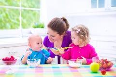 Moeder en jonge geitjes die ontbijt hebben Royalty-vrije Stock Fotografie
