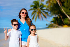 Moeder en jonge geitjes op een tropisch strand Royalty-vrije Stock Foto's