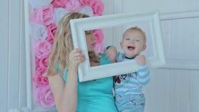 Moeder en jongen die door een kader kijken stock footage