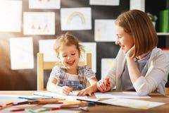 Moeder en kind de dochter trekt in creativiteit in kleuterschool Stock Foto's