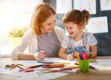 Moeder en kind de dochter trekt in creativiteit in kleuterschool Stock Afbeeldingen