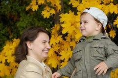 Moeder en kind in de herfstpari Royalty-vrije Stock Afbeeldingen
